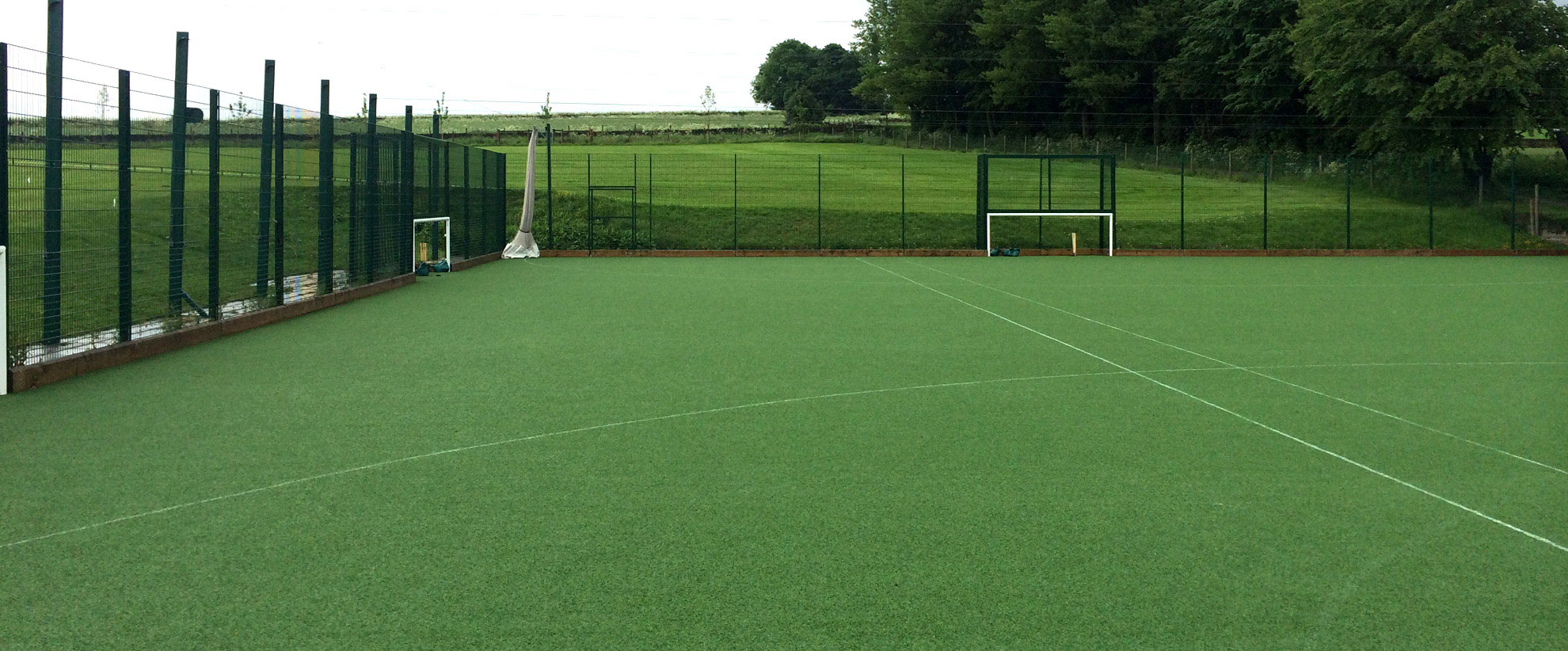 Multi-use games area pitch, with goal posts and exterior fencing.