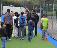 Children inspecting new non-turf cricket Practive Facility